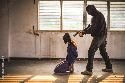 Photo A terrorist man holding gun kidnapping young women for a hostage in abandoned building