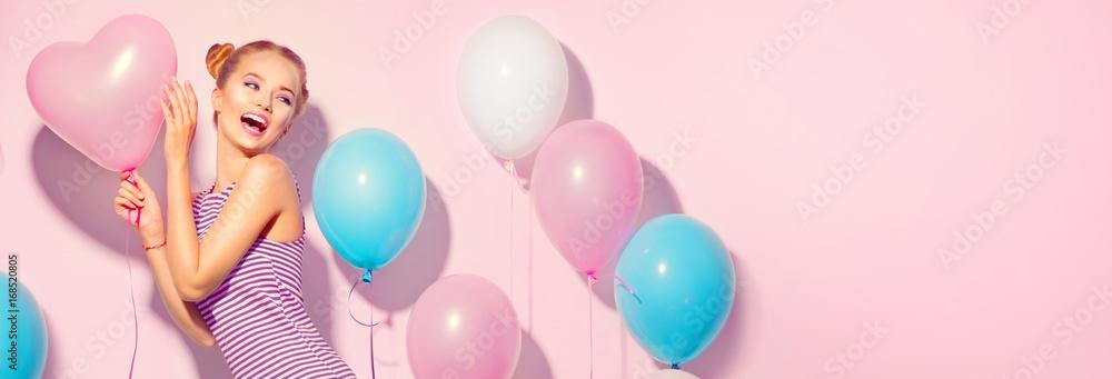 Fototapeta Beauty joyful teenage girl with colorful air balloons having fun over pink background