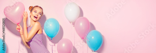 Beauty joyful teenage girl with colorful air balloons having fun over pink background
