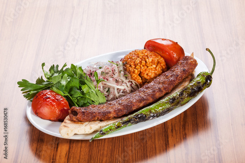 Turkish kebab served with yoghurt and vegetables on wooden table Wallpaper Mural
