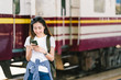 Asian female traveler, beautiful woman using map or social media check-in on smartphone at train station railway platform. Young tourist adventure, Asia tourism, Summer holiday railroad travel concept