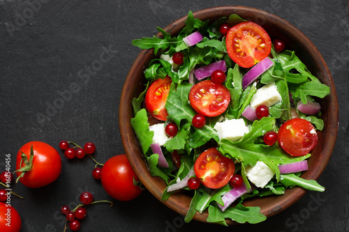 Leinwand Poster Fresh salad with arugula, feta cheese, red onion and red currant in a bowl