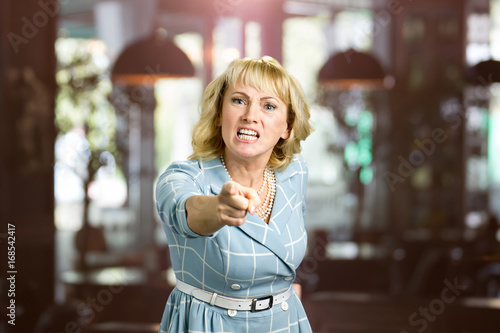 Unhappy yelling woman, blurred background. Frustrated middle aged woman shouting and threatening with index finger to someone, blurred background.