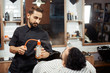 Barber spreading perfume on client