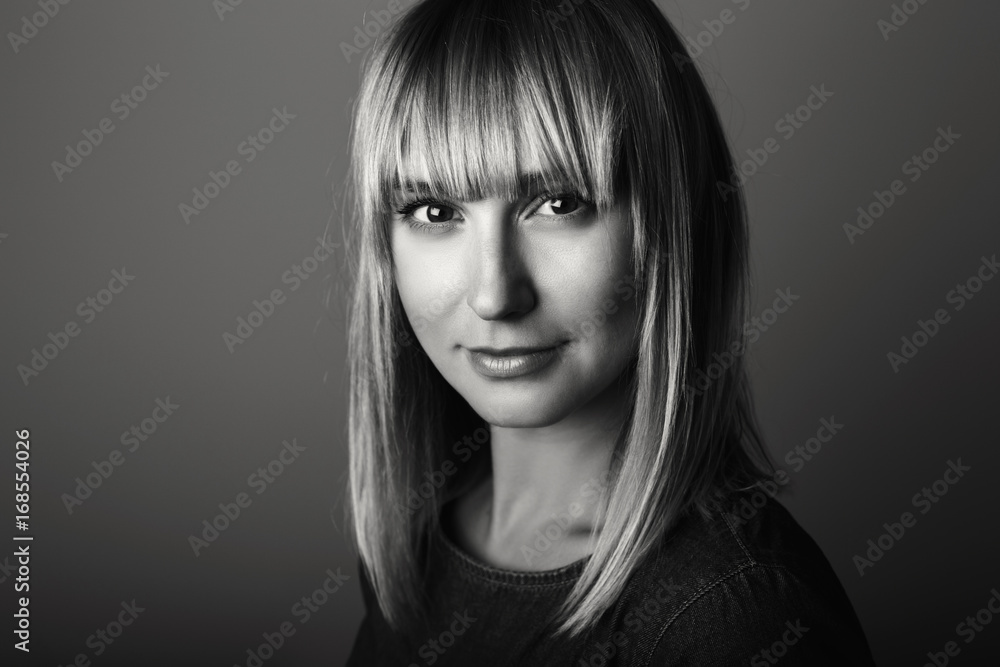 Fototapeta Closeup black-and-white portrait of beautiful young middle age blonde Caucasian woman looking in camera. Girl female with long blonde hair bob, studio beauty shot.