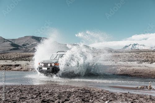 Fotografía  vehículo todoterreno cruzando un arroyo en el altiplano. Chile
