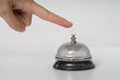 Hand is ringing silver service bell on white background.