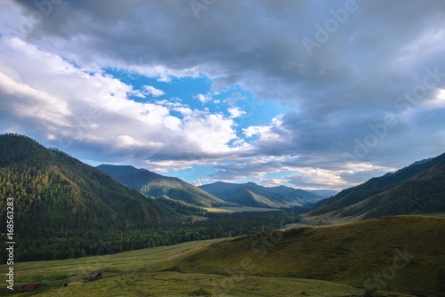 Spoed Foto op Canvas Grijze traf. fluffy rainy clouds over green hills at sunny day