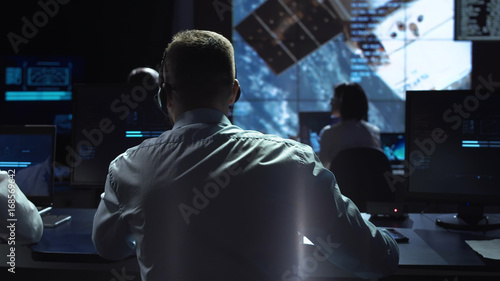Photo  Movement shot back view of man working on space mission in control center