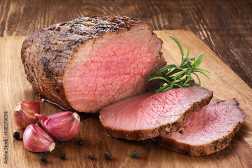 Photo Stands Meat Baked meat, garlic and rosemary on a wooden background. Roast beef.
