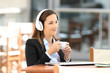 Businesswoman listening music in a coffee break