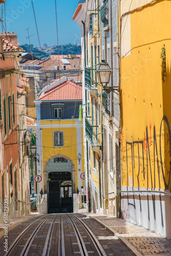 Spoed Foto op Canvas Mediterraans Europa Lisbon in Portugal, typical street, sloping alley with colored houses, cable car rails and typical pavement