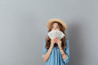 Excited young happy woman covering face with money