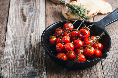 Fotografía  Roasted cherry tomatoes  in cast iron skillet