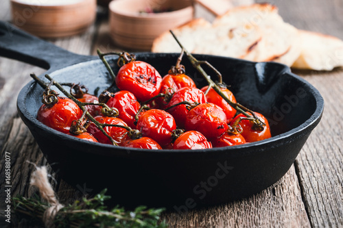 Fototapeta  Roasted cherry tomatoes  in cast iron skillet