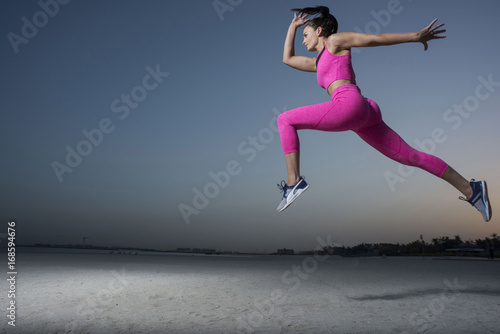 A side view of a strong athletic, beautiful female sprinter as she does a running jumping with an early morning sunrise and dark silhouettes of homes wearing a tight pink fitness outfit
