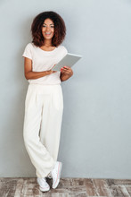 Full Length Of A Casual Smiling Afro American Woman Standing