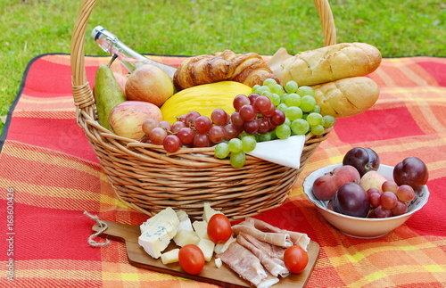 Tuinposter Picknick Basket with Food Fruit Bakery Cheese Ham Tomato Picnic Green Grass Summer Time Rest Background