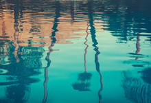 Background Image Of Palm Trees Reflected In Swimming Pool
