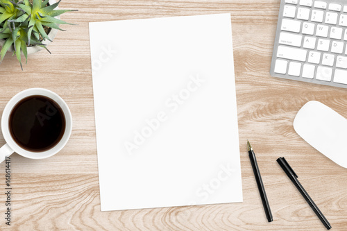 Fotografie, Obraz  Blank a4 paper is in the middle of wood office desk table with supplies