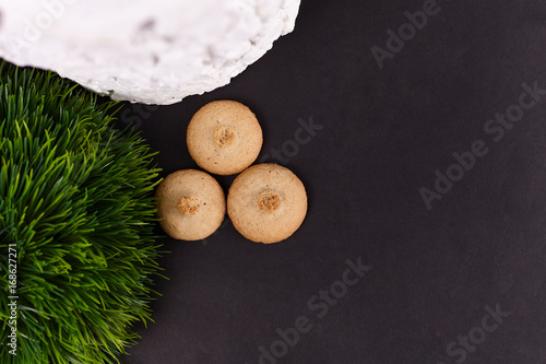 Fotografie, Obraz  Wheat cookies with white snag and artificial green grass on black background