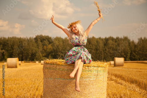 Fotografie, Obraz  beautiful rural woman wearing flower dress and wheat crown standing near dry rou