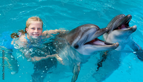 Fototapeta premium Happy child and dolphins in blue water. Dolphin Assisted Therapy