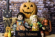 Two Child Dolls With Jars Of Halloween Candy Sitting In Front Of Straw Bale And Jack-o-lantern With Happy Halloween Sign