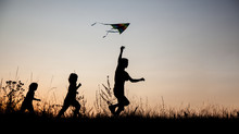 Children Playing Kite On Summer Sunset Meadow Silhouetted