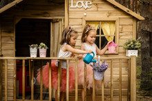 Two Girls Play With Watering Can In A Tree House