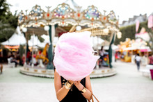 Young Woman Standing With Pink Cotton Candy Outdoors In Front Of The Carrousel At The Amusement Park
