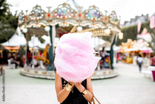 Foto op Plexiglas Amusementspark Young woman standing with pink cotton candy outdoors in front of the carrousel at the amusement park