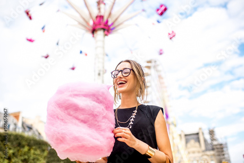 Poster Amusementspark Young woman standing with pink cotton candy in front of the ferris wheel at the amusement park