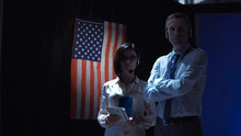 Confident Man And Woman In Formal Clothes Looking At Camera Standing At American Flag.