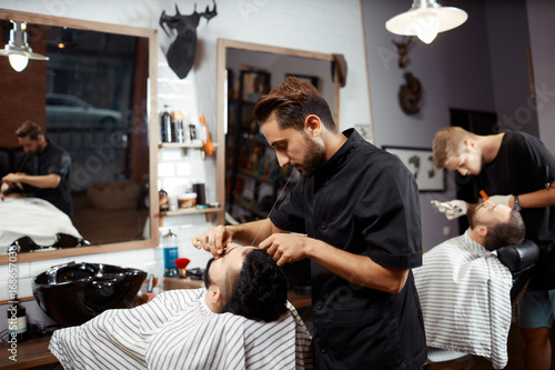Fotografija  Barber working with client in chair