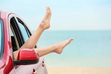 Legs Of Beautiful Young Woman Relaxing In Car At Sea Shore