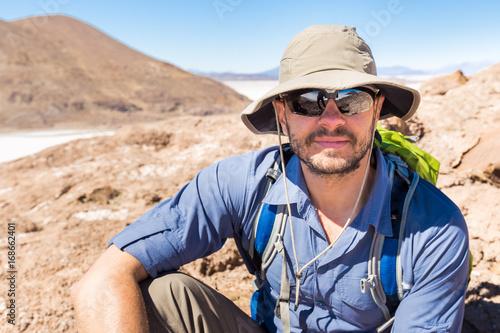 Man tourist portrain sitting  mountain Salar De Uyuni Bolivia.
