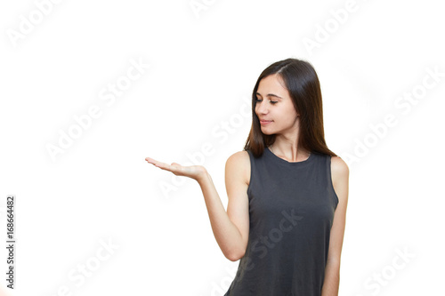 Fototapety, obrazy: Young excited woman standing happy smiling holding her hand showing something on the open palm. Girl emotions. White background.