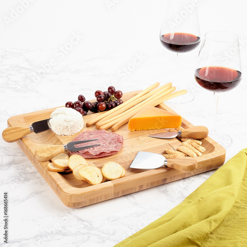 Bamboo wood serving tray with cheese and meats Poster