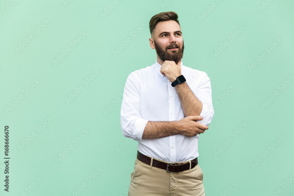 Fototapety, obrazy: Thoughtful bearded businessman looking away while standing against light green wall. Studio shot