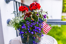 Patriotic Flower Pot With American Flags And Red And Blue Flowers On Porch