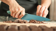 Woman hands chopping chocolate block for celebratory cake