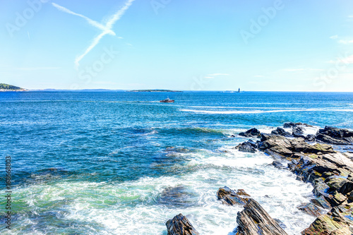 Cliff rocks with red boat by Portland Head Lighthouse in Fort Williams park in C Poster
