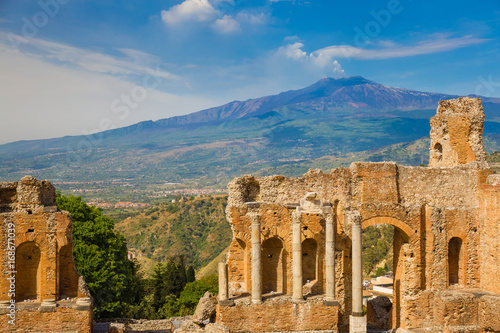 Poster Athens Panoramic view of beautiful town of Taormina with its greek amphitheatre and Etna volcano background, Sicily island, Italy