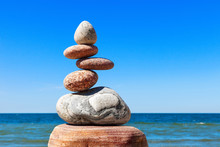 Stones Balance On A Background Of Blue Sky And Sea