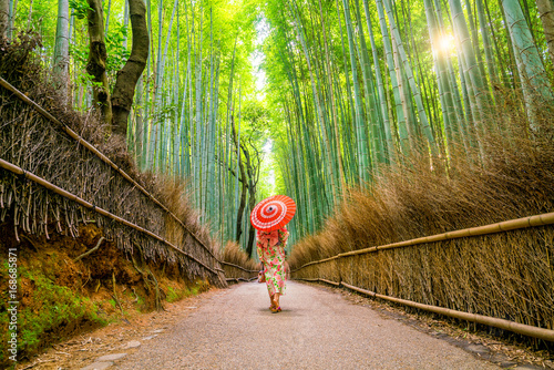 Poster Kyoto Woman in traditional Yukata with red umbrella at bamboo forest of Arashiyama
