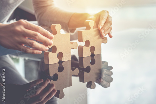 Fotografia  Closeup hand of woman connecting jigsaw puzzle with sunlight effect, Business so