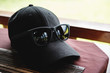 Black cap and black sunglasses on the table