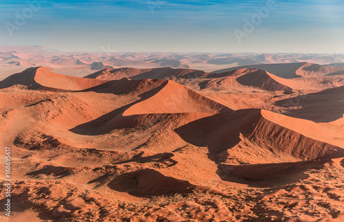 Namib desert, Sossusvlei. Aerial panorama of the big red dunes in Sossusvlei area taken from the helicopter. Annual growth of the area of sand. Global warming on the planet.
