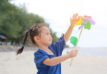 Child Girl With A Spinning Pinwheel On The Beach.
